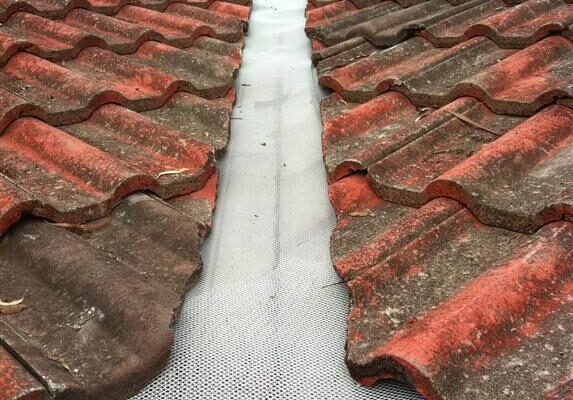 Completed gutterguard installation to the roof valleys of a tile roof.